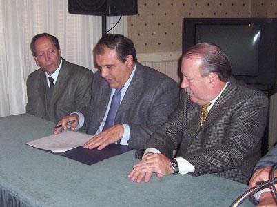 Carlos Ben Presidente de AYSA firma el convenio ante la atenta mirada de Osvaldo Amieiro