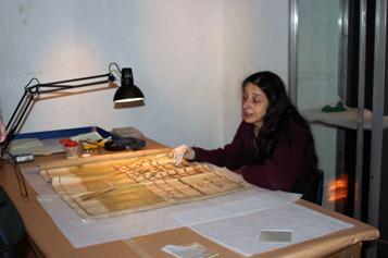 Nora Altrudi en el minucioso trabajo de restauración de un antiguo plano