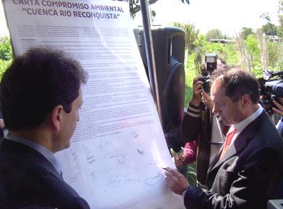 Scioli firma el compromiso ante la atenta mirada de Sergio Massa