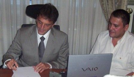 Sergio Massa firma el decreto ante la mirade de Omar Cabral