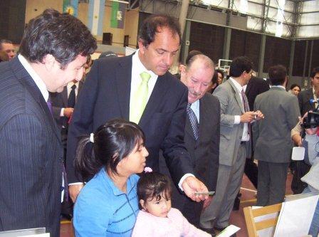 Arroyo, Scioli y Amieiro entrgan la tajeta a una beneficiaria