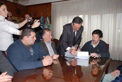 El intendente Posse firmando ante el titular de la línea 33 y los representantes de los trabajadores el convenio que permitirá a la empresa seguir operando en el puerto
